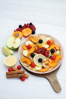 Uma vista superior distante frutas fatiadas frescas coloridas e maduras na mesa de madeira e foto de comida colorida de frutas de fundo branco