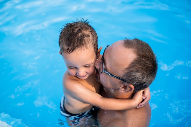 Uma vista superior do pai segurando o filho pequeno na piscina ao ar livre.