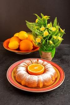 Uma vista superior doce redondo bolo com açúcar em pó isolado dentro da placa, juntamente com limões e fundo cinza biscoito de açúcar