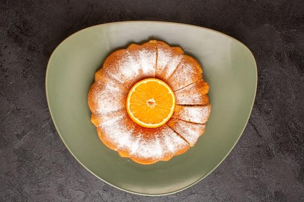 Uma vista superior doce redondo bolo com varinha de açúcar em pó laranja no meio fatiado doce delicioso prato interior e no fundo cinza