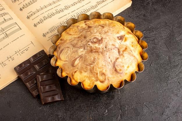Uma vista superior, doce, redondo, bolo, gostoso, delicioso, dentro, bolo, panela, junto, com, barras chocolate, sobre, a, fundo cinzento, biscoito, biscoito açúcar