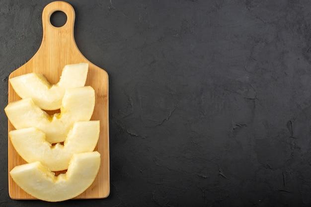 Uma vista superior em pedaços de melão fresco, suculento e doce, alinhado em madeira escura