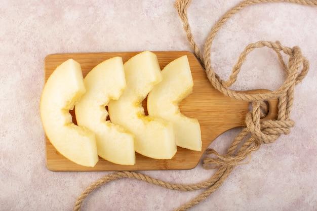 Uma vista superior em pedaços de melão fresco, suculento e doce, forrado com cordas em uma mesa de madeira