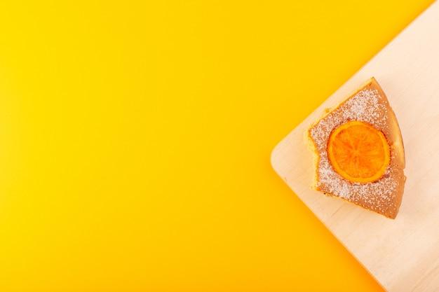 Uma vista superior fatia de bolo de laranja doce delicioso saboroso na mesa de madeira de creme e fundo amarelo biscoito de açúcar doce