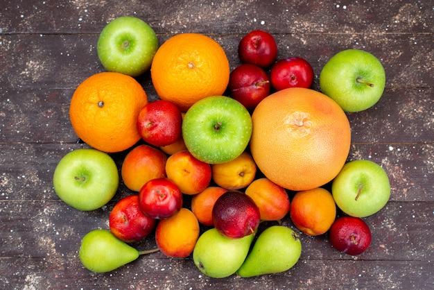 Uma vista superior frutas maçãs frescas peras ameixas laranjas no fundo escuro composição de frutas cor do arco-íris