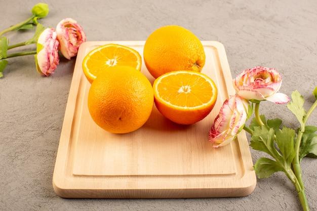 Uma vista superior laranjas frescas azedo maduro fatiado e todo maduro cítrico suculento tropical vitamina amarelo sobre a mesa de creme