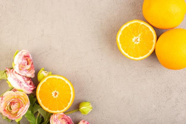 Uma vista superior laranjas frescas azedo maduro fatiado e todo maduro cítrico tropical vitamina amarelo junto com flores secas na mesa de creme