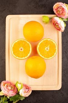 Uma vista superior laranjas frescas azedo maduro inteiro e fatiado com rosas secas cítrico maduro tropical vitamina amarelo na mesa escura
