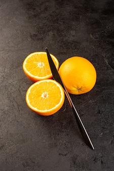Uma vista superior laranjas frescas azedo maduro inteiro e fatiado maduro citrino tropical vitamina amarelo na mesa escura