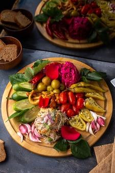 Uma vista superior legumes fatiados e pepinos inteiros alface na mesa de madeira marrom junto com nacos de pão nas plantas de vitaminas de mesa cinza