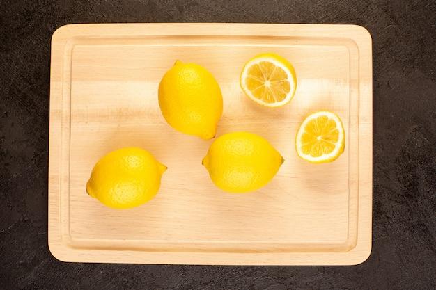 Uma vista superior limões frescos azedo maduro inteiro e fatiado cítrico maduro tropical vitamina amarelo na mesa escura