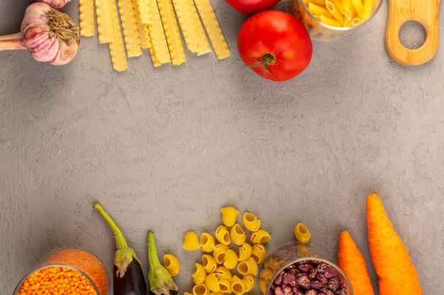 Uma vista superior macarrão cru amarelo seco italiano longo macarrão, juntamente com tomates vermelhos, berinjelas, cenouras e alho, isolado no fundo cinza legumes comida refeição