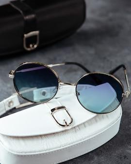 Uma vista superior modernos óculos de sol azuis sobre o fundo cinza isolado elegância espetáculos visão