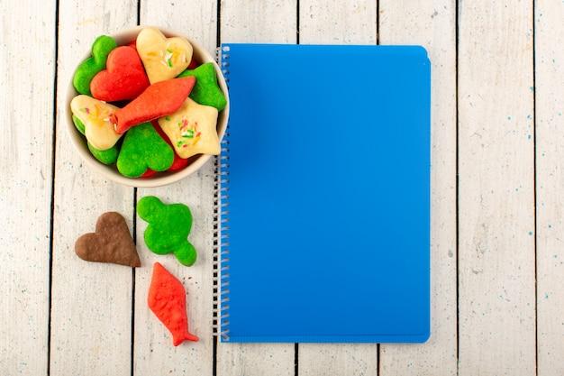 Uma vista superior multicoloridos deliciosos biscoitos diferentes formados placa interna com caderno azul na superfície cinza