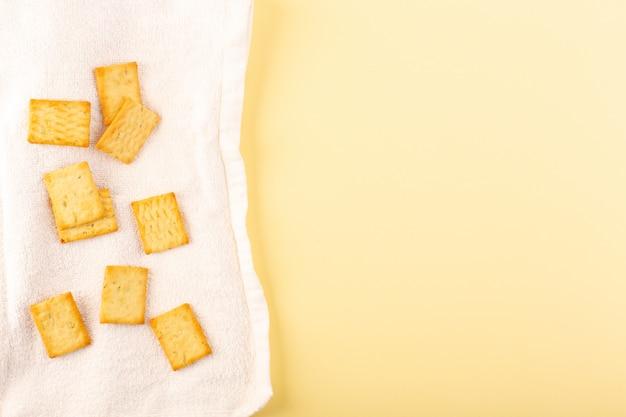 Uma vista superior pouco batatas fritas salgadas isolado rachaduras no tecido branco e o creme coloriu o fundo lanche torrado do biscoito