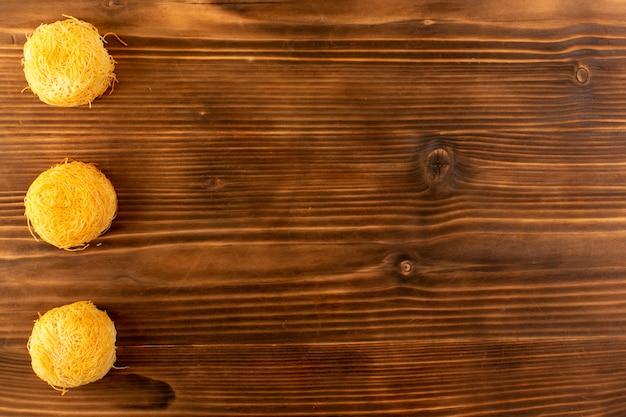 Uma vista superior redonda bolos doces deliciosos bolos saborosos isolados alinhados na mesa rústica de madeira marrom açúcar doce biscoito