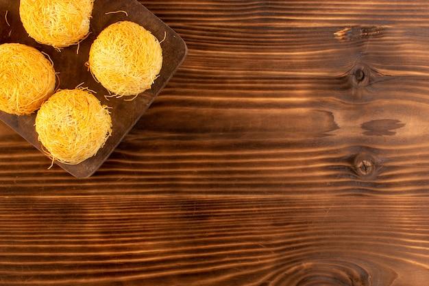 Uma vista superior redonda bolos doces deliciosos bolos saborosos isolados alinhados na mesa rústica de madeira marrom e fundo marrom biscoito doce de açúcar