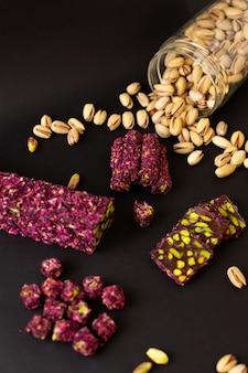 Uma vista superior roxo doce bar gostoso gostoso junto com amendoins na superfície escura
