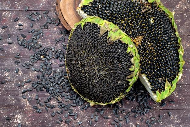 Uma vista superior sementes de girassol pretas frescas e saborosas muito sobre o óleo de lanche marrom de sementes de girassol de grãos de mesa