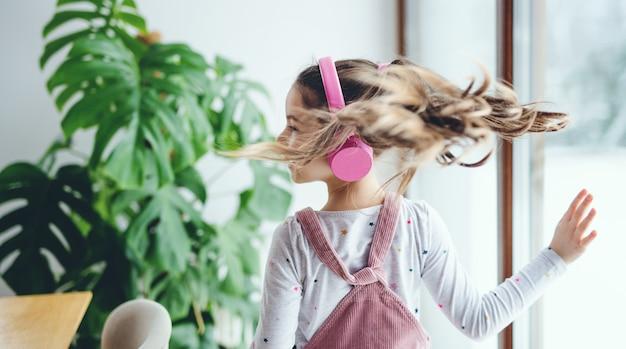 Uma vista traseira da alegre menina pequena com fones de ouvido dentro de casa em casa, ouvindo música.