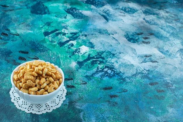 Uma vitrine de bolachas de peixe em uma tigela, sobre a mesa de mármore.