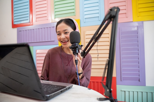 Uma vlogger segurando um microfone enquanto grava um podcast com um laptop