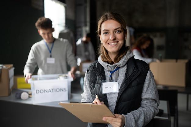 Uma voluntária trabalhando em um centro comunitário de doação de caridade, olhando para a câmera.