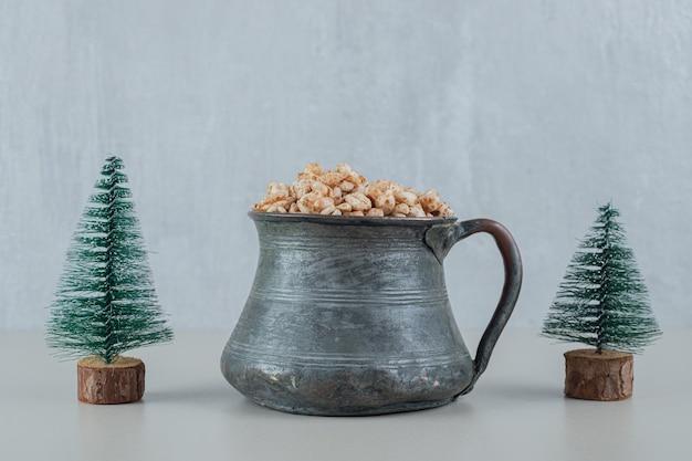 Uma xícara antiga cheia de cereais saudáveis com árvores de natal.