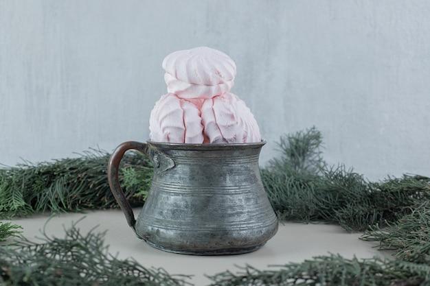 Uma xícara antiga cheia de zéfiros brancos e rosa.