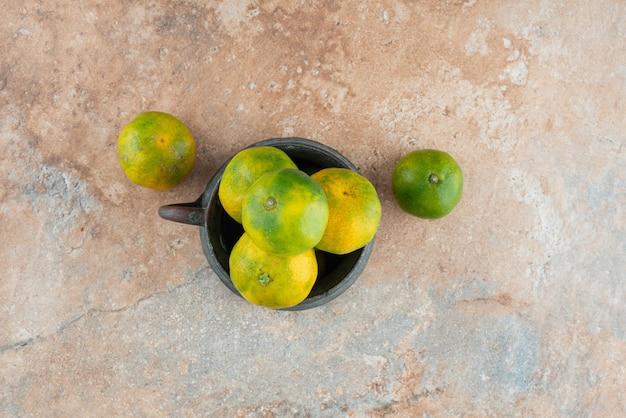 Uma xícara antiga com tangerinas azedas em mármore