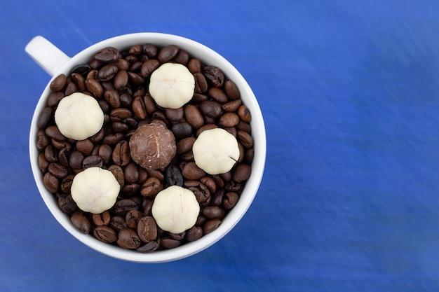 Uma xícara branca cheia de grãos de café com biscoitos na superfície azul