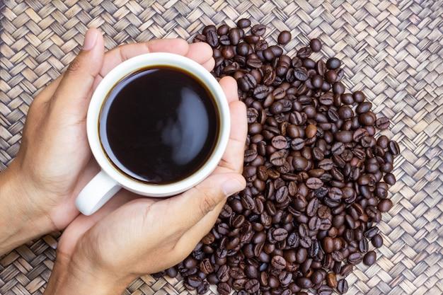 Uma xícara branca de café nas mãos do homem com grãos de café ao lado dele.