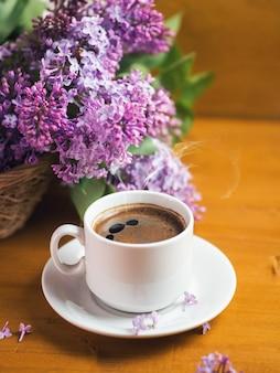 Uma xícara branca de café perfumado em uma mesa de madeira, um lilás florescendo em uma cesta. maio chegou