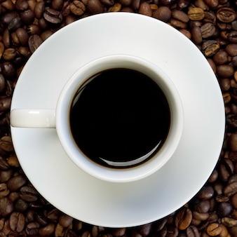 Uma xícara branca de café preto em uma superfície cheia de grãos de café