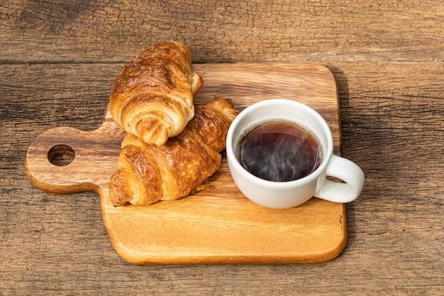 Uma xícara branca de café quente com croissant na mesa de madeira