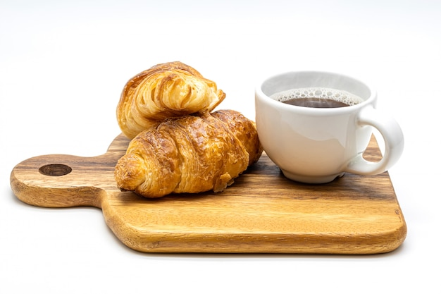 Uma xícara branca de café quente com croissant no isolado de madeira da bandeja no fundo branco.