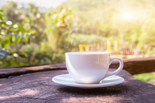 Uma xícara branca de canecas de café expresso quentes colocadas em um piso de madeira com neblina matinal e montanhas