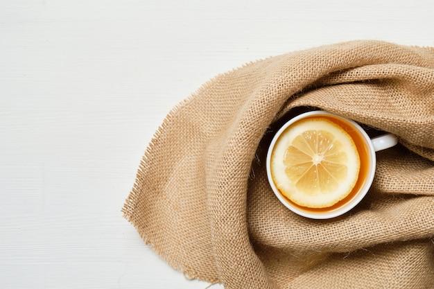 Uma xícara branca de chá com limão no fundo de linho