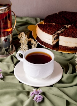 Uma xícara branca de chá e chaleira com bolo de chocolate oreo.