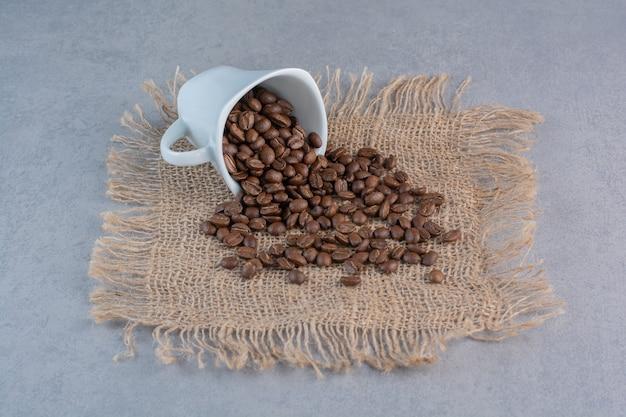 Uma xícara branca de grãos de café torrados na superfície de mármore.