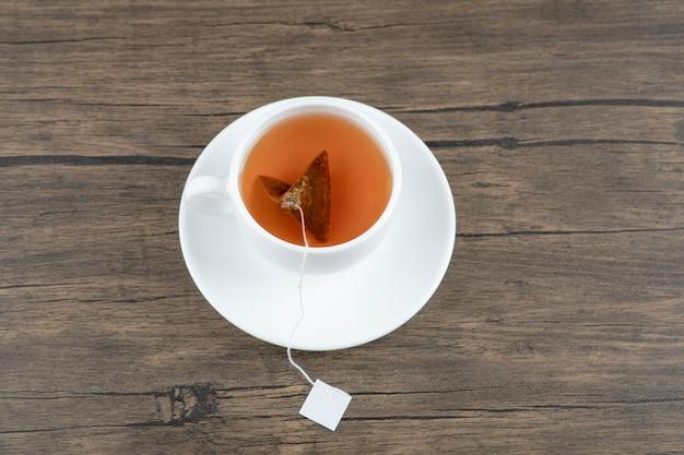 Uma xícara branca de saboroso chá quente com saquinho de chá em uma mesa de madeira.