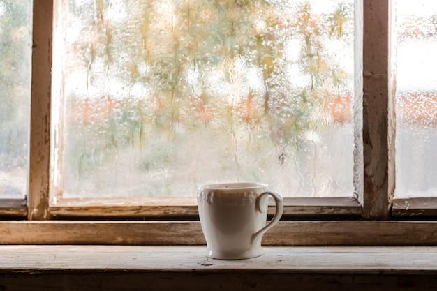 Uma xícara branca e livros velhos sobre uma janela molhada de madeira rústica