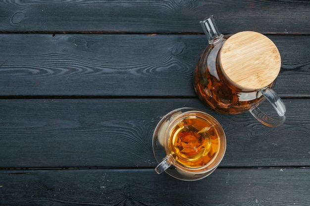 Uma xícara com chá e bule de chá na mesa