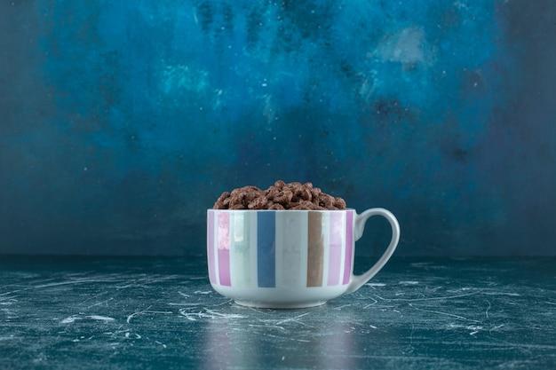 Uma xícara de anéis de milho, no fundo azul. foto de alta qualidade