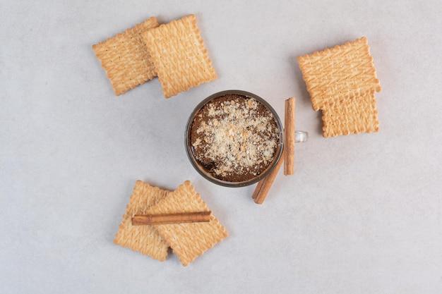 Uma xícara de bebida deliciosa com biscoitos e canela em pau. foto de alta qualidade
