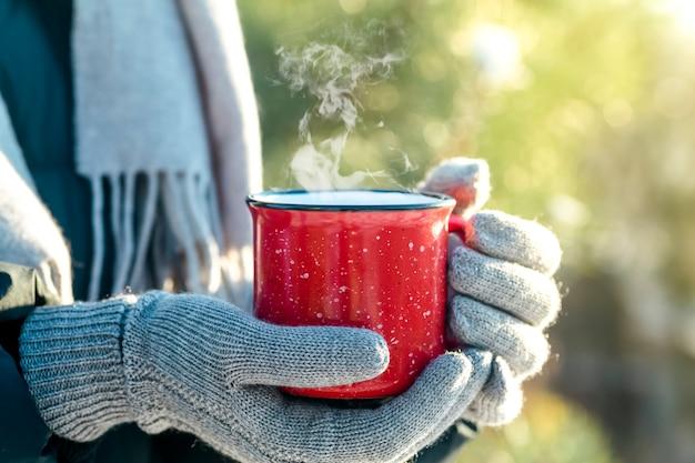 Uma xícara de bebida quente (chá, café ou vinho quente) na natureza do inverno. mão feminina com uma xícara vermelha. o inverno relaxa o conforto e o humor.