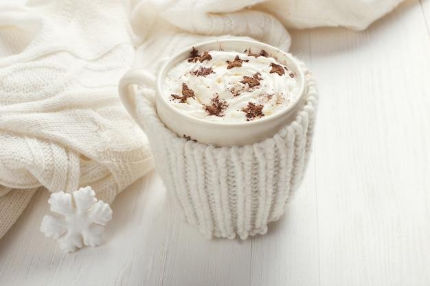 Uma xícara de bebida quente de inverno com chantilly em uma mesa de madeira