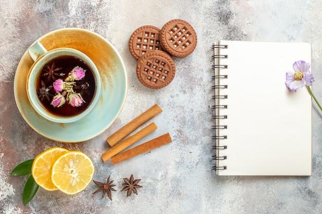 Uma xícara de biscoitos de chá de ervas e rodelas de limão e limão com canela e um caderno na mesa branca