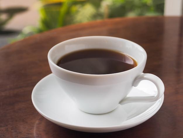 Uma xícara de café americano quente ou café expresso quente na mesa de madeira.