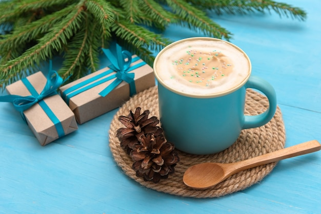 Uma xícara de café azul sobre uma mesa de madeira azul clara na noite de natal.